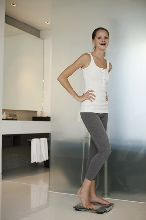 Woman standing on weight scale Stock Photo - 13450835