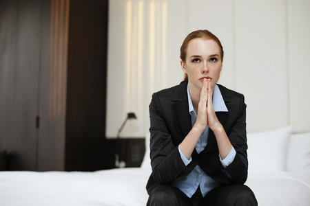 Businesswoman sitting on bed contemplating Stock Photo - 13450862
