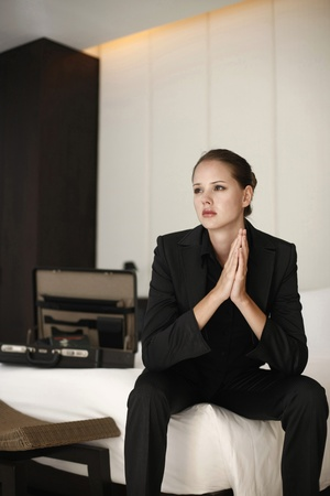 Businesswoman sitting on bed contemplating photo