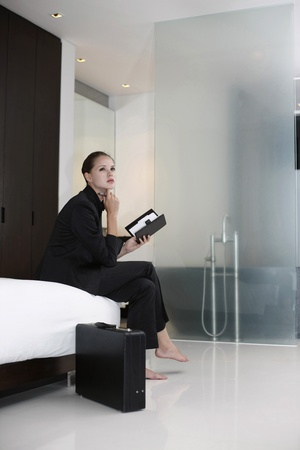 Businesswoman sitting on bed holding organizer photo