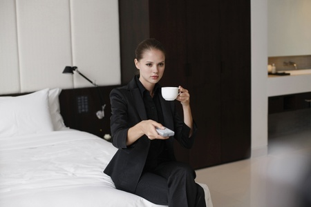 Businesswoman enjoying a cup of coffee with remote control in hand photo