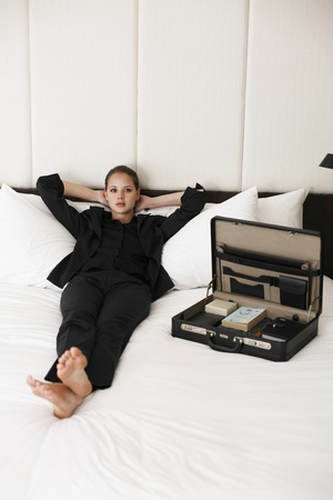 Businesswoman relaxing on bed with briefcase at the side photo