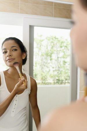 Woman applying makeup in the bathroom photo