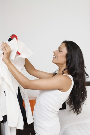 coathanger: Woman holding clothes on hangers