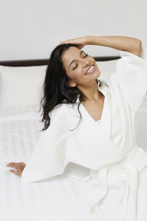 Woman in bathrobe sitting on the bed photo
