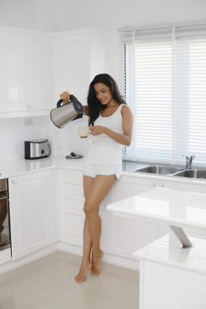 kettles: Mujer vertiendo agua caliente en la taza Foto de archivo