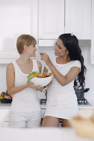Women sharing a bowl of salad Stock Photo - 13360406