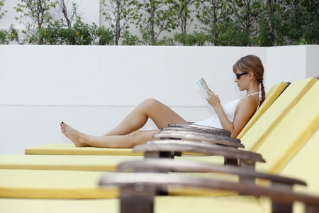 Woman reading and relaxing by the pool side photo