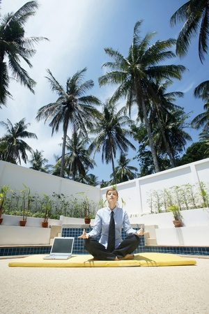 Businesswoman meditating by the pool side photo