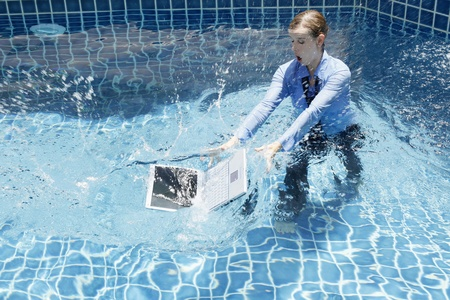 savings risk: Businesswoman trying to save her laptop from the swimming pool