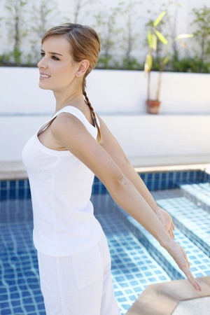 Woman stretching by the pool side photo