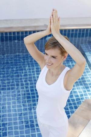 Woman practising yoga by the pool side Stock Photo - 13360434