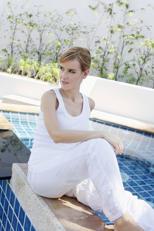 Woman sitting by the pool side photo