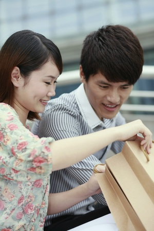 Man and woman looking into paperbag Stock Photo - 13360263