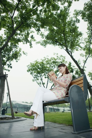 Woman sitting on bench reading book photo