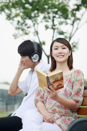 Man listening to music on the headphones, woman reading book photo