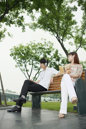sitting on a bench: Man listening to music on the headphones, woman with book looking at man Stock Photo