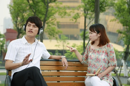 Man listening to music on the headphones, woman scolding man Stock Photo - 13361479