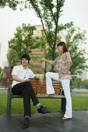 sitting on a bench: Man listening to music on the headphones, woman scolding man