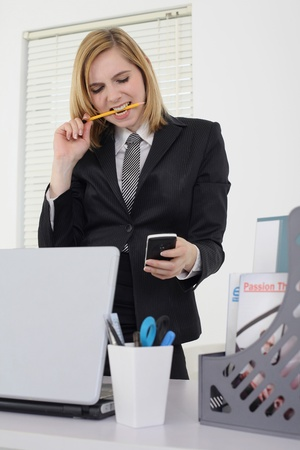 three people only: Businesswoman biting on pencil while reading text message on phone