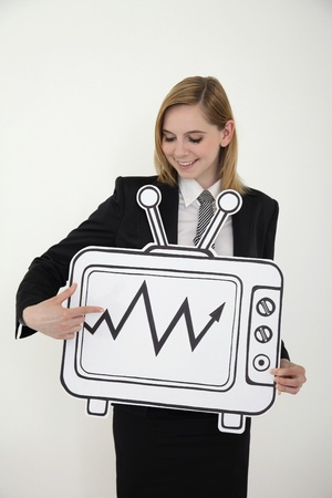 Businesswoman pointing at stock market growth on television Stock Photo - 13360412