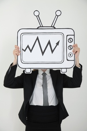 Businesswoman holding television indicating stock market growth over her face photo