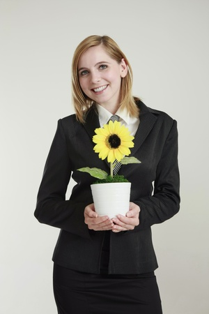 Businesswoman holding sunflower in pot photo
