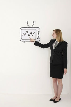 woman pointing up: Businesswoman pointing at stock market growth on television Stock Photo