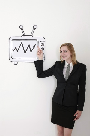 Businesswoman pointing at stock market growth on television Stock Photo - 13360185