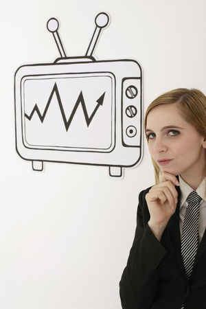 Businesswoman with hand on chin beside television Stock Photo - 13360127