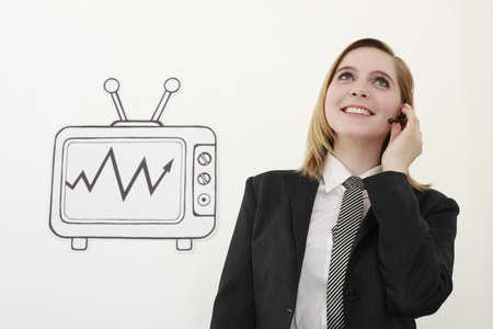 Businesswoman talking on headset beside television Stock Photo - 13359705