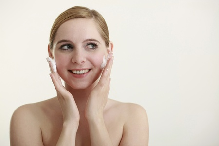 Woman washing her face with facial cleanser photo