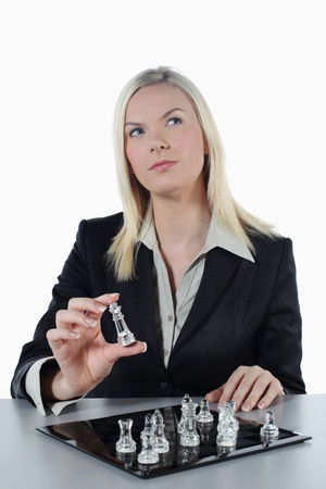 british ethnicity: Businesswoman thinking while holding chess piece
