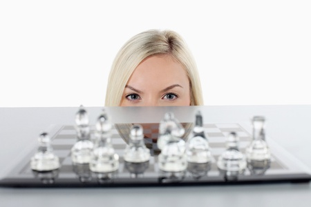 Businesswoman peeking from under the table, chess set on the table photo