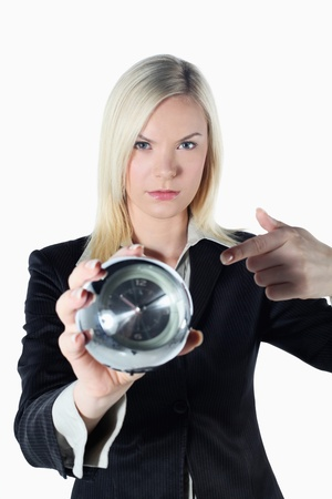 british ethnicity: Businesswoman pointing at an alarm clock