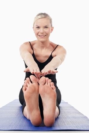 descalza: Mujer se extiende en la estera de yoga Foto de archivo