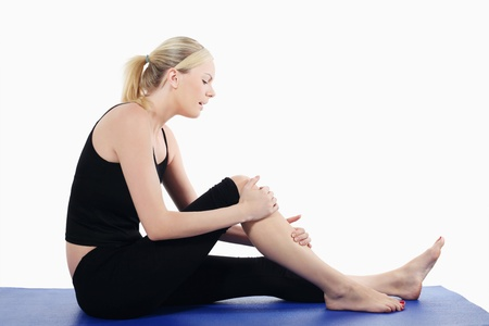 british ethnicity: Woman holding her knee while sitting on yoga mat
