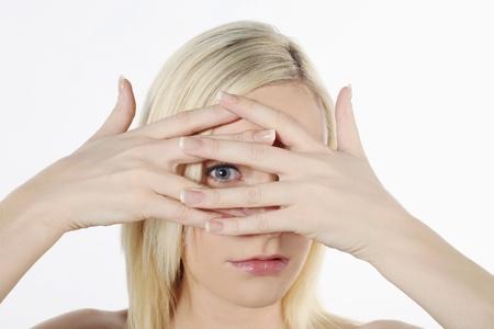 young fear: Woman peeking in between her fingers Stock Photo