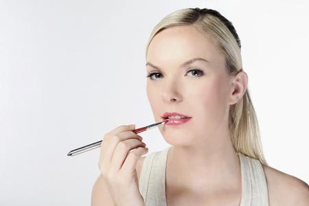 self conceit: Woman applying lip color using lip brush