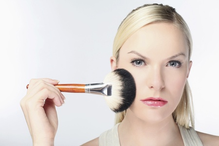 Woman applying powder on face with make-up brush photo