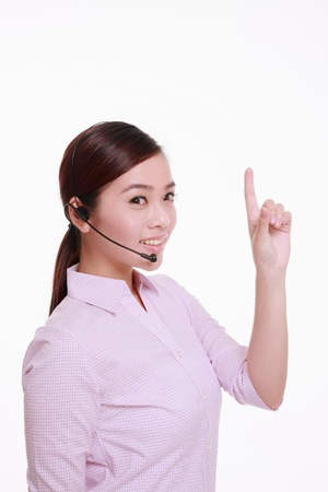 Businesswoman talking on telephone headset and pointing photo