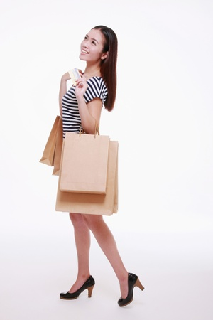 Woman holding credit card and shopping bags Standard-Bild