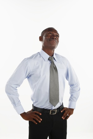 arms akimbo: Businessman with arms akimbo looking up Stock Photo