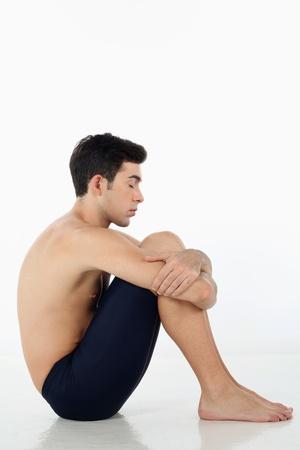 Man sitting on the floor hugging his knees photo