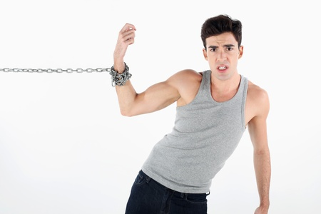 Man with hand tied to a chain, pulling hard photo