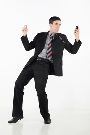 western attire: Businessman grooving while listening to music on MP3 player