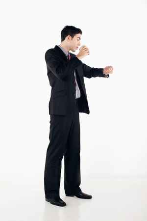 western attire: Businessman drinking while checking time on his watch