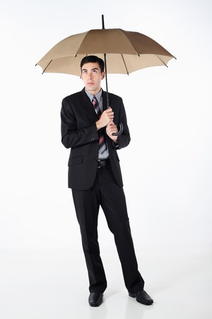 Businessman holding an umbrella and looking up photo