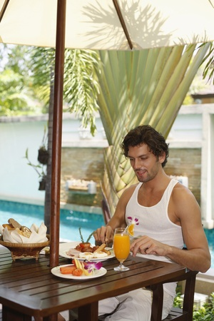 Man having breakfast by the pool photo