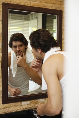 Man examining himself in front of the mirror photo